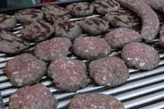 Variety of different kind of meat steaks, meatballs, shish kebab, fillet, burgers and sausages with bread on a grill outdoor. Gril. Led meat on a barbecue Royalty Free Stock Photography