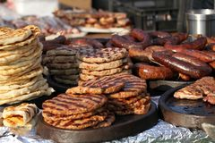 Variety of different kind of meat steaks, meatballs, shish kebab, fillet, burgers and sausages with bread on a grill outdoor. Gril. Led meat on a barbecue Royalty Free Stock Photo