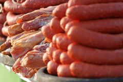 Variety of different kind of meat steaks, meatballs, shish kebab, fillet, burgers and sausages with bread on a grill outdoor. Grilled meat on a barbecue Stock Photography