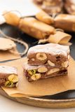 A variety of different nutty nougat in dark chocolate with roasted hazelnuts cut open to show the nougat mix on a wooden royalty free stock photos