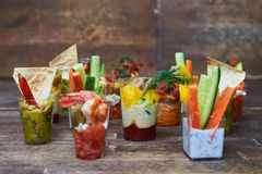 Variety of different tasty appetizers presented in small glasses Stock Image