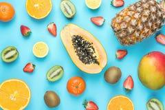 Variety of Different Tropical Summer Fruits. Papaya Mango Tangerines Citrus Oranges Pineapple Lemons Strawberries Kiwi on Blue stock photos