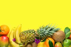 Variety of Different Tropical and Seasonal Summer Fruits. Pineapple Mango Coconut Citrus Oranges Lemons Apples Kiwi Bananas. Arranged in Lower Border on Yellow stock image