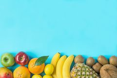 Variety of Different Tropical and Seasonal Summer Fruits. Pineapple Mango Coconut Oranges Lemons Apples Kiwi Bananas on Blue. Variety of Different Tropical and stock image