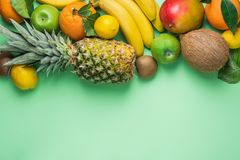 Variety of Different Tropical and Summer Fruits. Pineapple Mango Coconut Citrus Oranges Lemons Apples Kiwi Bananas on Turquoise Royalty Free Stock Images