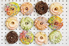 Variety of donuts on a peg board. Variety of colorful old fashioned fried gourmet donuts with glaze on a peg board stock photography