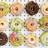 Variety of donuts on a peg board. Variety of colorful old fashioned fried gourmet donuts with glaze on a peg board royalty free stock photos