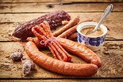 Variety of dried spicy sausages with mustard. Variety of dried spicy sausages with a pot of mustard for dipping on old rustic wooden boards in a close up view Stock Photos