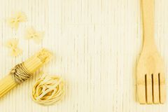 Variety of dry pasta, spaghetti and wooden spoon on the table royalty free stock images