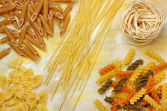 Variety of dry raw pastas over painted textile background. Overhead view Stock Image