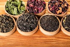 Variety of dry teas. In wooden bowls stock photo