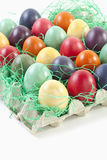 Variety of Easter eggs in egg carton on white background Royalty Free Stock Image