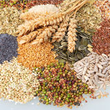 Variety of edible seeds with ears of wheat. Variety of edible seeds with ripe golden ears of wheat including whole and dehusked sunflower, sesame, poppy, linseed Stock Photography