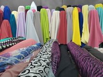 Variety of fabrics in different colors displayed in a shop. Variety of colors, textured background, abstract multicolored, material for clothing and decoration Royalty Free Stock Photo