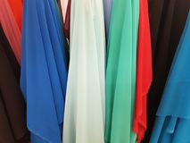 Variety of fabrics in different colors displayed in a shop. Variety of colors, textured background, abstract multicolored, material for clothing and decoration Royalty Free Stock Photos