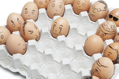 Variety of facial expressions painted on brown eggs arranged in carton Stock Photos