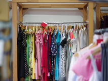 Variety of female`s clothes hanging on racks in a luxury boutique. Shopping sale theme. Consumerism concept. Royalty Free Stock Photography