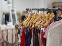 Variety of female`s clothes hanging on racks in a luxury boutique. Shopping sale theme. Consumerism concept. A big assortment colorful clothes for women on a Royalty Free Stock Photography