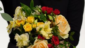 Variety of flowers in the bouquet. Florist. White. Close up. Florist gathers some flowers and makes a festive bouquet, flower arrangement in different colors, on stock footage