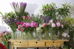 Variety of flowers in vases on display in flower shop Stock Image