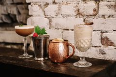 A variety of four alcoholic cocktails against white brick background stock image