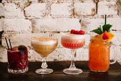 A variety of four alcoholic cocktails against white brick background. A variety of four alcoholic cocktails on a wooden table against white brick background royalty free stock image