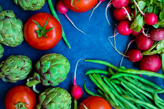 Variety of fresh colorful organic vegetables green beans, tomatoes, red radish, artichokes on dark blue background, copy space Stock Photos
