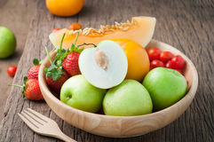Variety fresh fruits on wood plate and fork,strawberry,melon,tomatoes. mix variety high fructose fruits on kitchen table. healthy. Eating and dieting food stock images