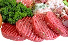 Variety of fresh meat. Garnished with lettuce and parsley, studio shot Royalty Free Stock Photography