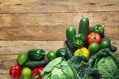 Variety Fresh Organic Green Vegetables Savoy Cabbage Zucchini Cucumbers Red Yellow Bell Peppers Avocados on Weathered Plank Wood. Variety Fresh Organic Green Stock Photography