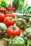 Variety of Fresh Organic Vegetables Artichokes Green Beans Tomatoes Red Radish Broccoli on Wood Garden Kitchen Table Vegan royalty free stock photo