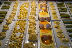 Variety of fresh pasta types showcase for dinner including pappardelle, ravioli, etc. on white rectangle plate at night. Selective focus, Mykonos, Greece Stock Photos