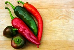 Variety of fresh peppers  on wooden table with copy space Stock Image