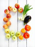 Variety of fresh summer fruits and vegetables - apples, peaches, tomatoes and eggplants. Copy space for your text Royalty Free Stock Photo