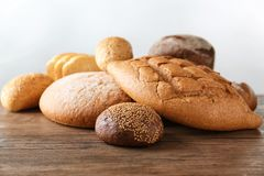 Variety of fresh tasty bread on wooden table. Against light background Royalty Free Stock Images