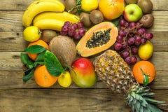 Variety of Fresh Tropical and Summer Seasonal Fruits Pineapple Papaya Mango Coconut Oranges Kiwi Bananas Lemons Grapefruit on Wood Royalty Free Stock Images