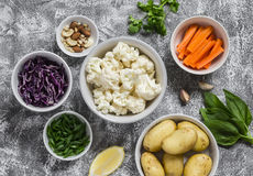 Variety of fresh vegetables in bowls - potatoes, red and cauliflower, spinach, green onions, carrots, nuts, olive oil, cilantro. Raw ingredients. Vegan table stock images