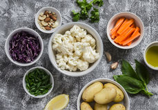 Variety of fresh vegetables in bowls - potatoes, red and cauliflower, spinach, green onions, carrots, nuts, olive oil, cilantro. Raw ingredients. Vegan table stock photography