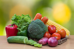Variety of fresh vegetables on wood table. Paprika, lettuce, broccoli, carrot, corn, tomatoes, onion and slice cucumber on wood table Stock Photography