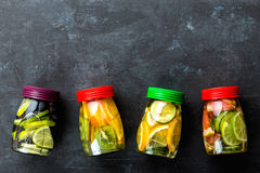 Variety of fruit infused detox water in jars for a healthy diet top view on a dark background. With space for text Royalty Free Stock Photo