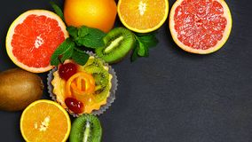 Variety of fruits grapefruit, oranges, kiwi, lemon, mint bunched together on a shale board, the concept of healthy eating, copy sp. Ace, top view set stock images