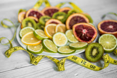 A variety of fruits and measuring tape. On white background ,concept of health and nutrition Royalty Free Stock Photos