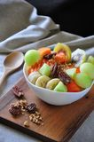 Variety Fruits on Yogurt Bowl with Pecan on Wooden Board. Variety fruits on yogurt bowl with pecan put on wooden board royalty free stock photo