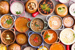 Variety of Garnished Soups in Colorful Bowls. High Angle View of Various Comforting and Savory Gourmet Soups Served in Bread Bowls and Handled Dishes and Topped Royalty Free Stock Images