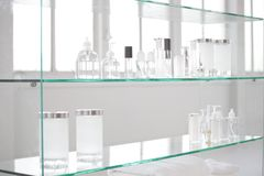 Variety of glass bottles on glass shelf. A lot of size and shape of glass bottles put on a glass shelf in a hygienic laboratory stock photo