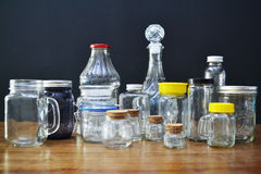 Variety of glass jars and bottles. Various types of glass jars and bottles on a wooden table Royalty Free Stock Photography
