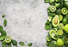 Variety of green fruits and vegetables on a concrete or stone ba. Variety of green fruits and vegetables with on a grey concrete,stone or slate background.Top stock photos