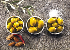 Variety of green olives on a gray stone Stock Photos
