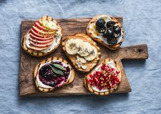 Variety grilled bread dessert small plates sandwiches with cream cheese and apple, pomegranate, jam, grapes, peanut butter, banana royalty free stock photo