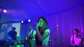 The young singer performs at the festival. The girl is singing at the wedding. Performance rock group at the event. The variety group performs at the event in stock video